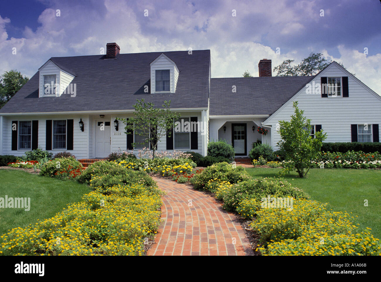cape cod style house and entrance flower garden with welcoming stock