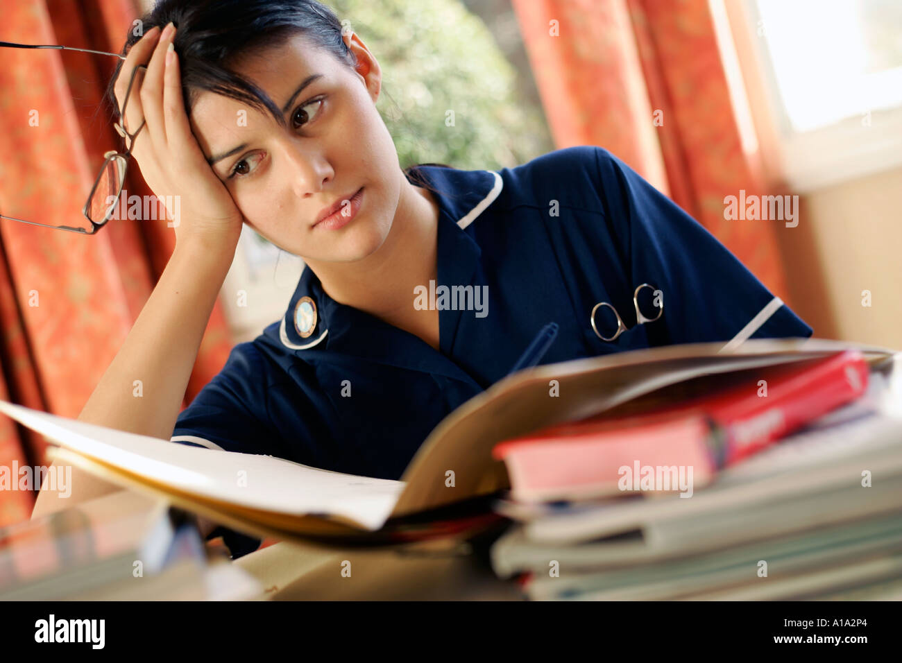 Nurse looking tired as she revises for exams - Stock Image