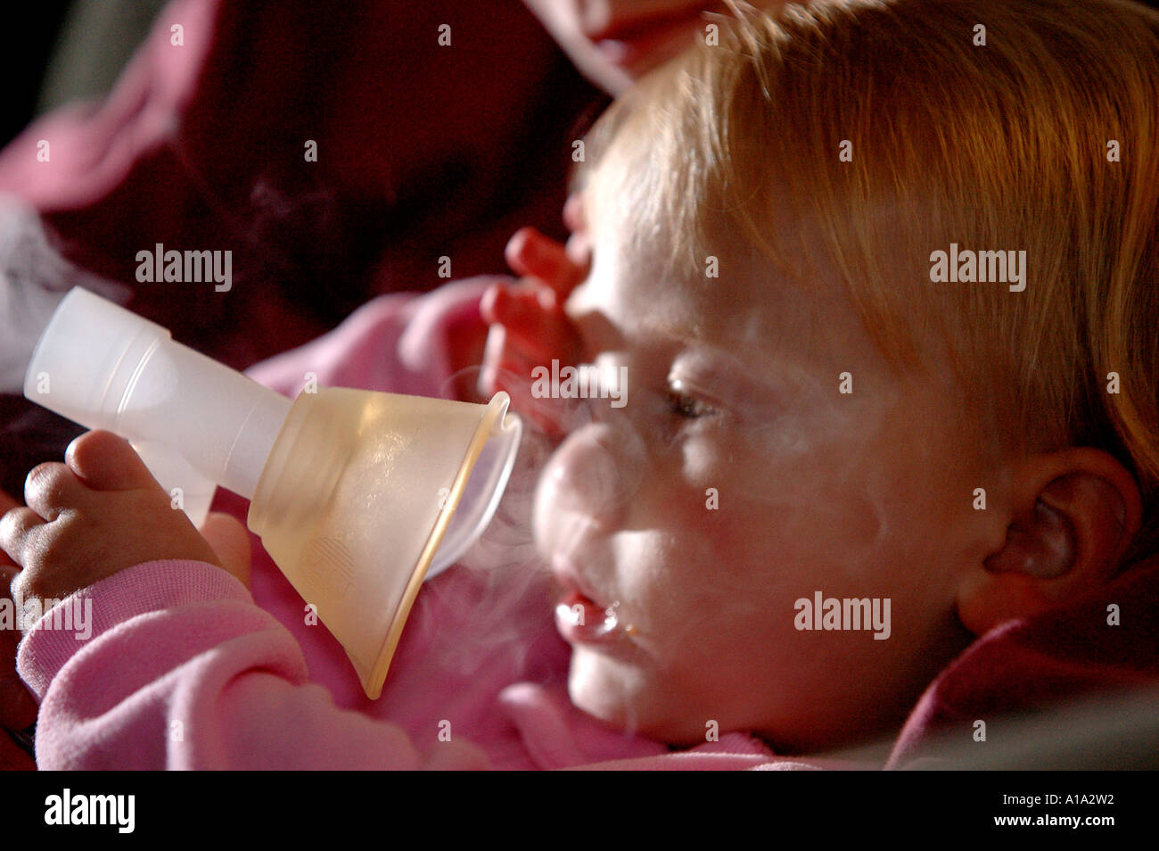 A child uses a nebulizer for her asthma. - Stock Image