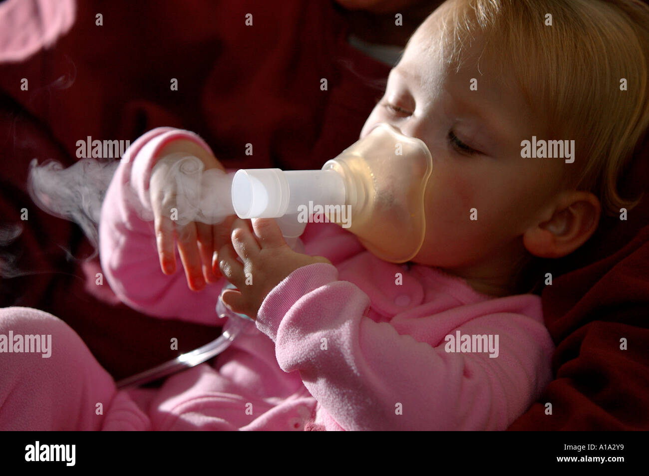 A toddler takes her medicine through a nebulizer as part of treatment for asthma. - Stock Image