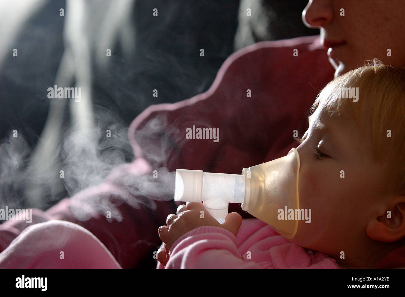 A toddler sits on her mother's lap as she takes her medicine through a nebulizer as part of treatment for asthma. - Stock Image