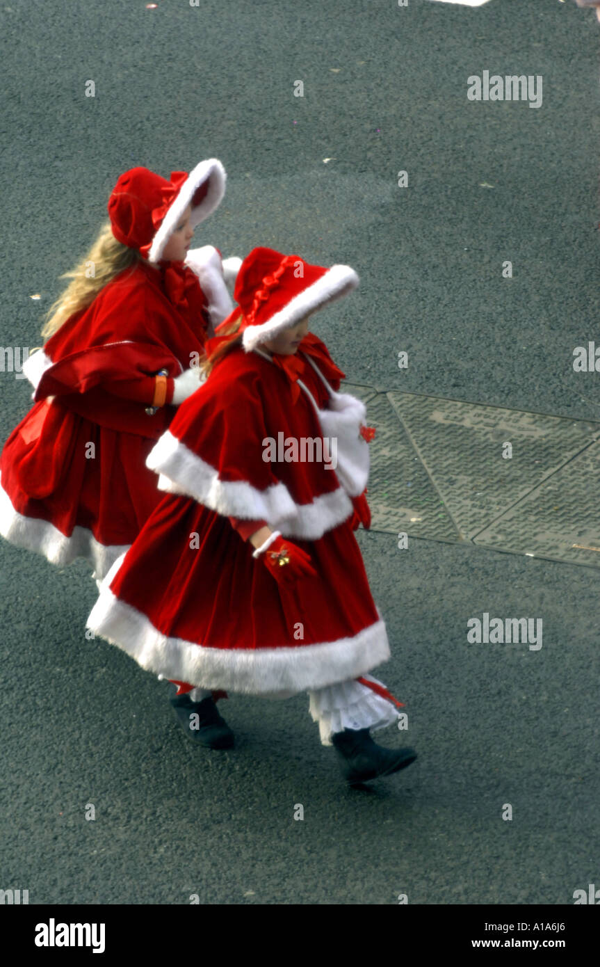 two girls in red christmas outfits santa girls young cute pretty - Stock Image