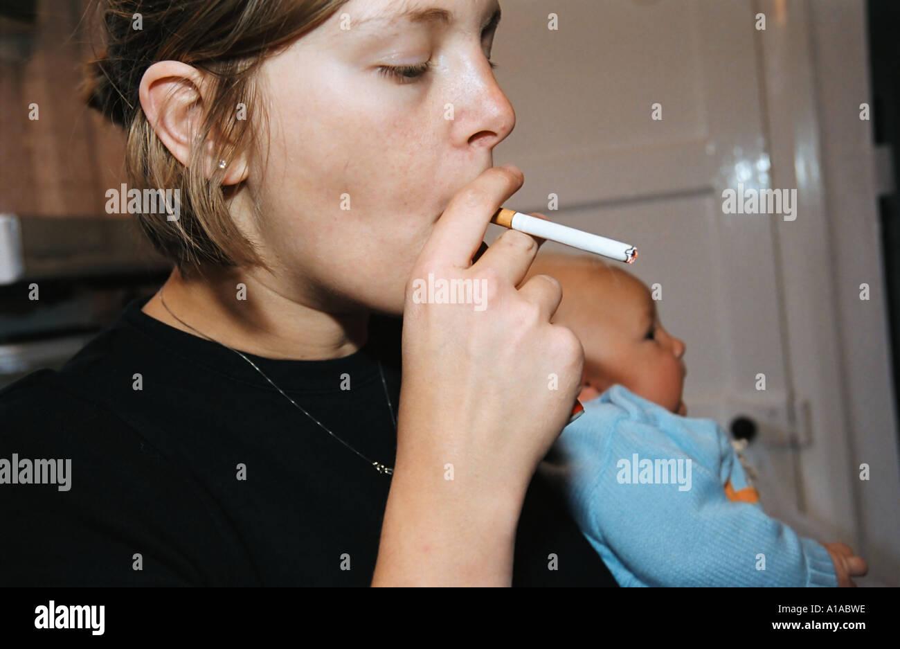 Woman smoking in kitchen - Stock Image