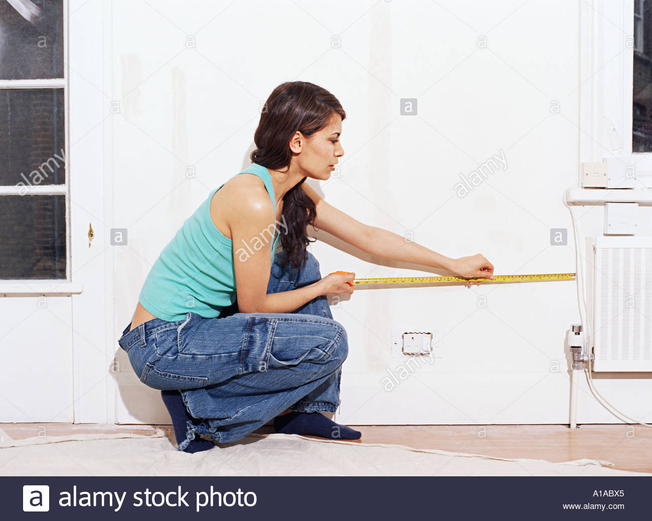 Woman measuring wall - Stock Image