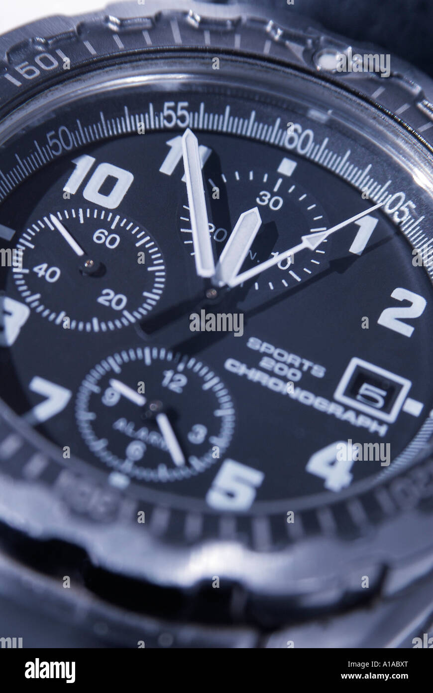 A chronograph shows five minutes before twelve, symbol for date, deadline, term - Stock Image