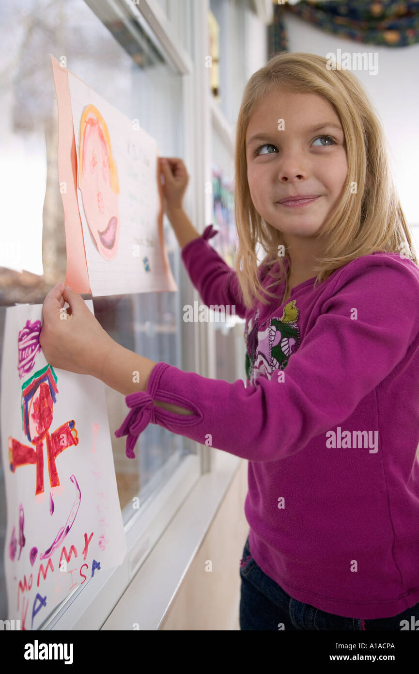 Girl holding drawing of face - Stock Image