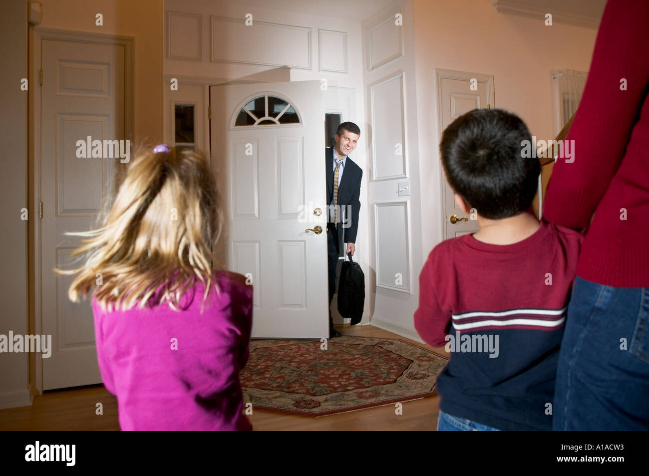 Family greeting businessman as he arrives home - Stock Image