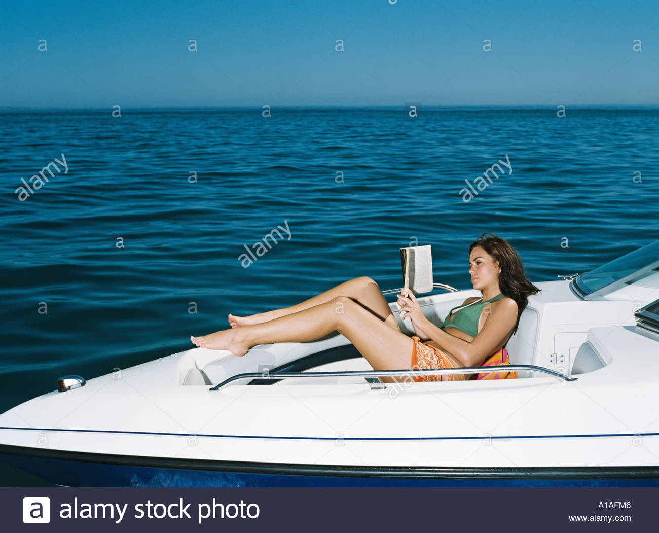 Woman on speedboat reading a book - Stock Image