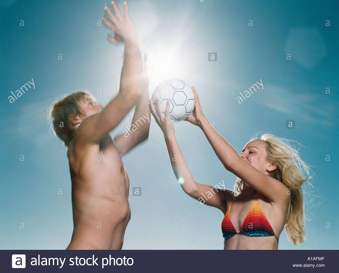 Young man and woman playing volleyball - Stock Image