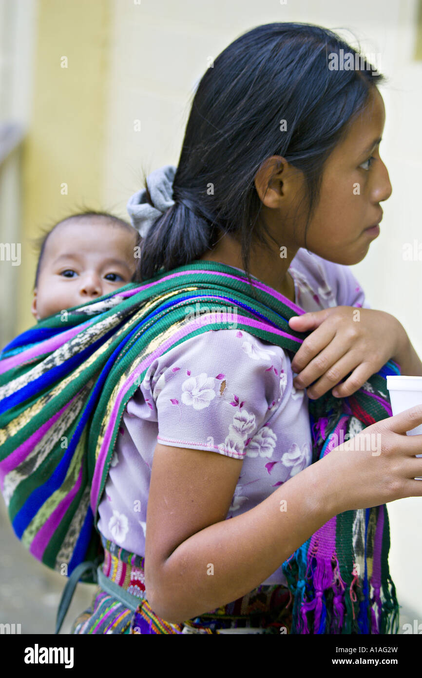 GUATEMALA SAN PEDRO LA LAGUNA Indigenous Tzutujil Mayan teenaged girl iin traditional dress carries her baby brother - Stock Image