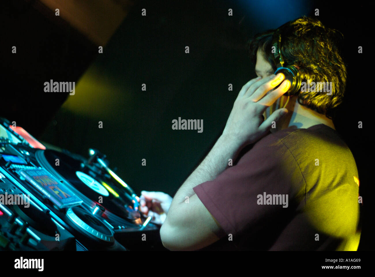 Club DJ Behind the Decks of a Nightclub Cutting in a Track on a Turntable - Stock Image