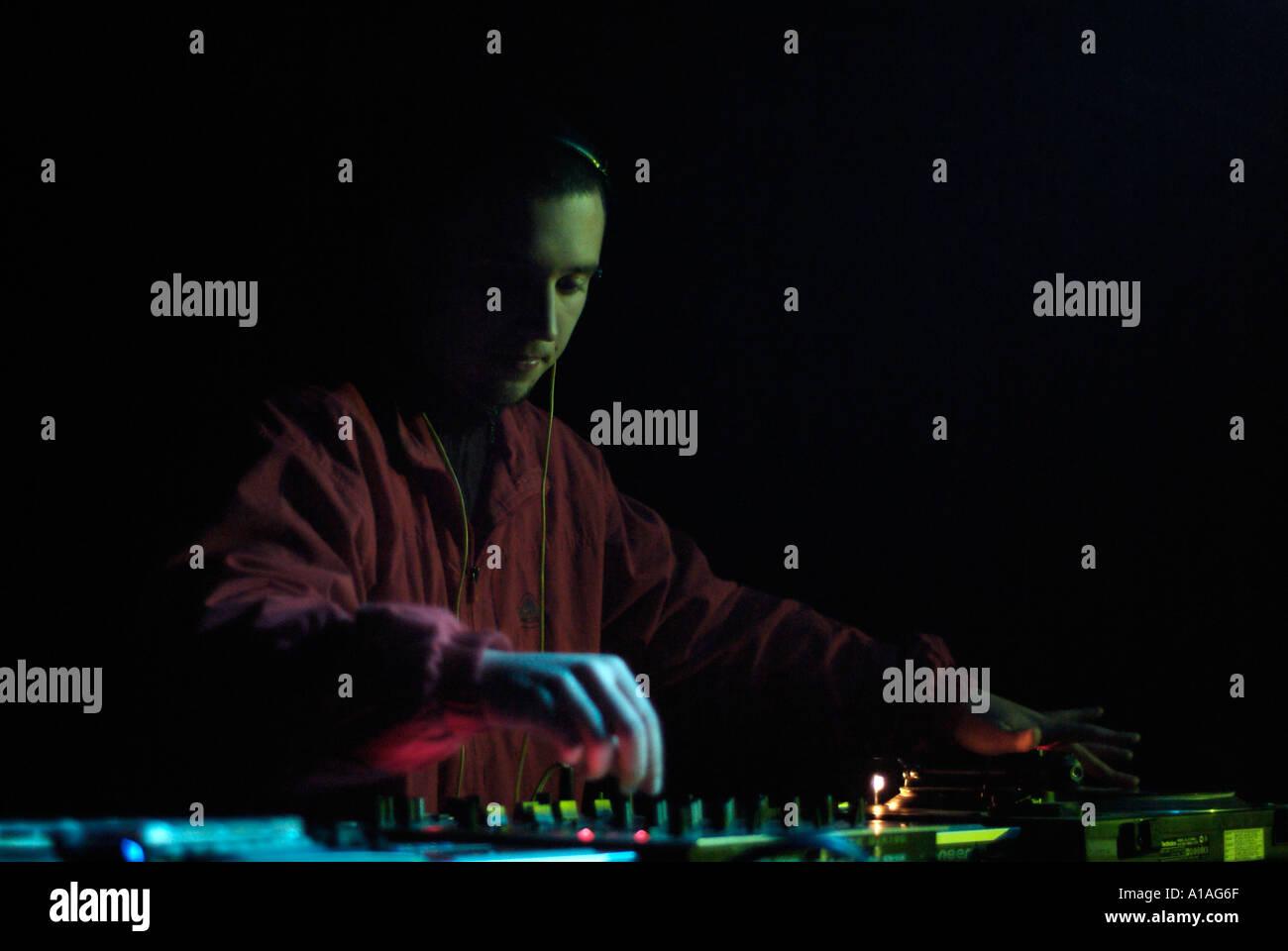Club DJ Behind the Decks of a Nightclub - Stock Image