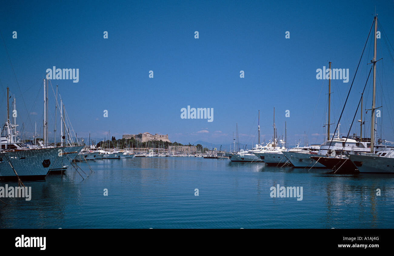 Yachts of the wealthy moored at Antibes with Fort Carre in the background - Stock Image