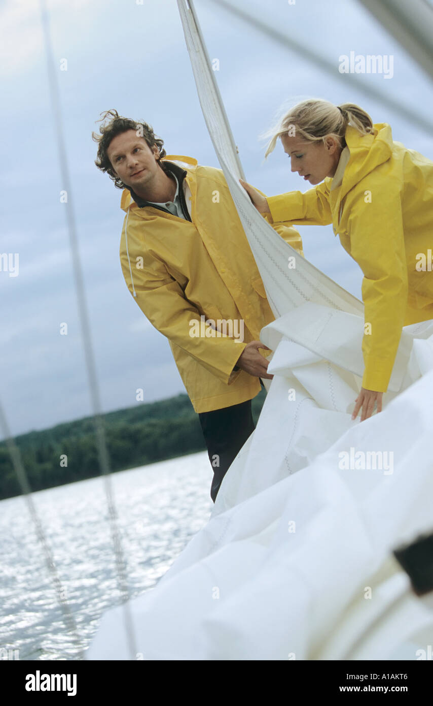 Couple taking down sail on boat - Stock Image