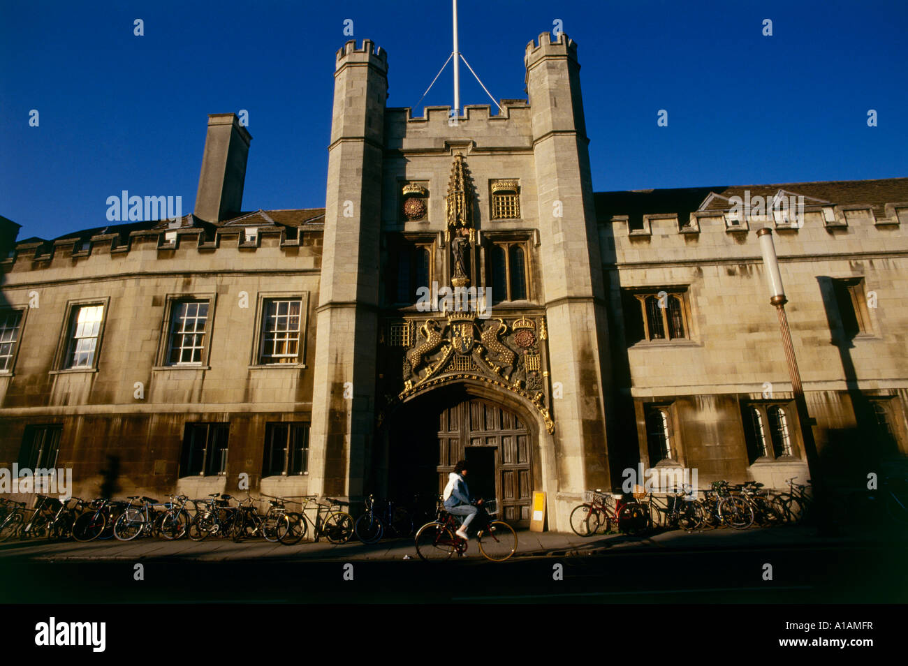 A student cycles past the main gate at Christ s College Bicycles are stacked against the college walls Cambridge - Stock Image