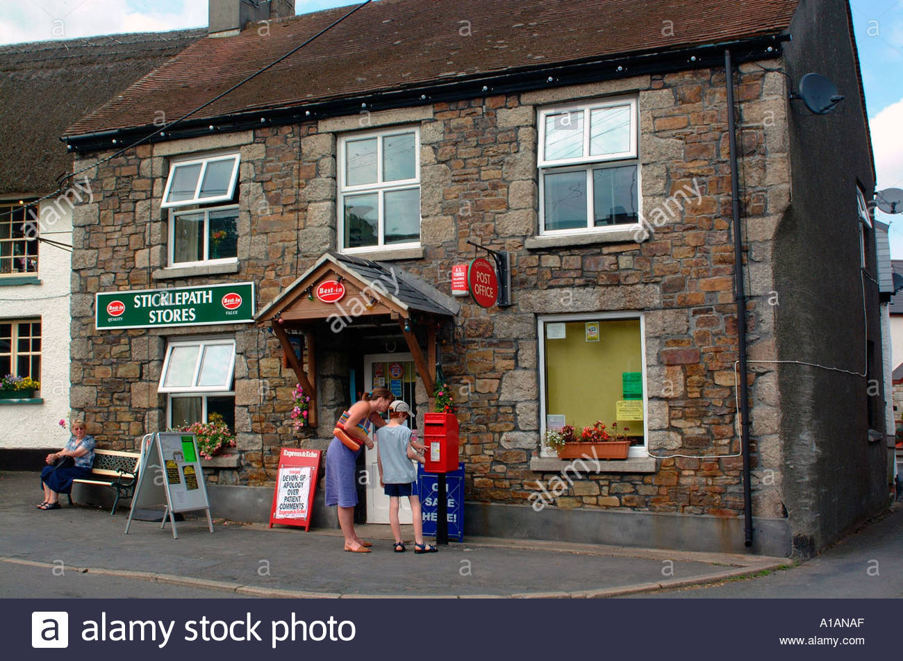 Woman child outside rural village post office and stores Sticklepath Devon UK - Stock Image