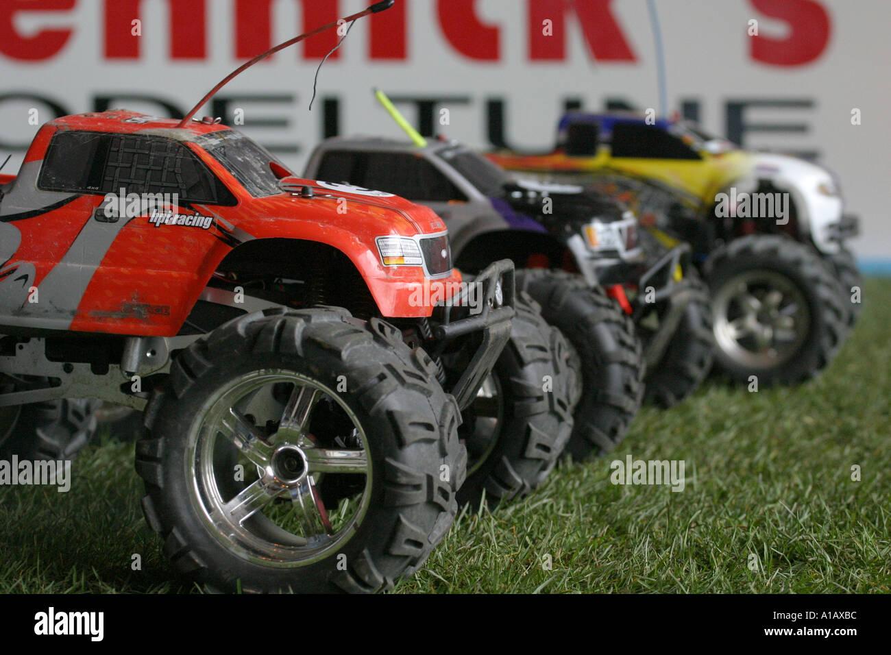 Radio control racing monster truck cars on grid on indoor grass track Belfast Northern Ireland - Stock Image