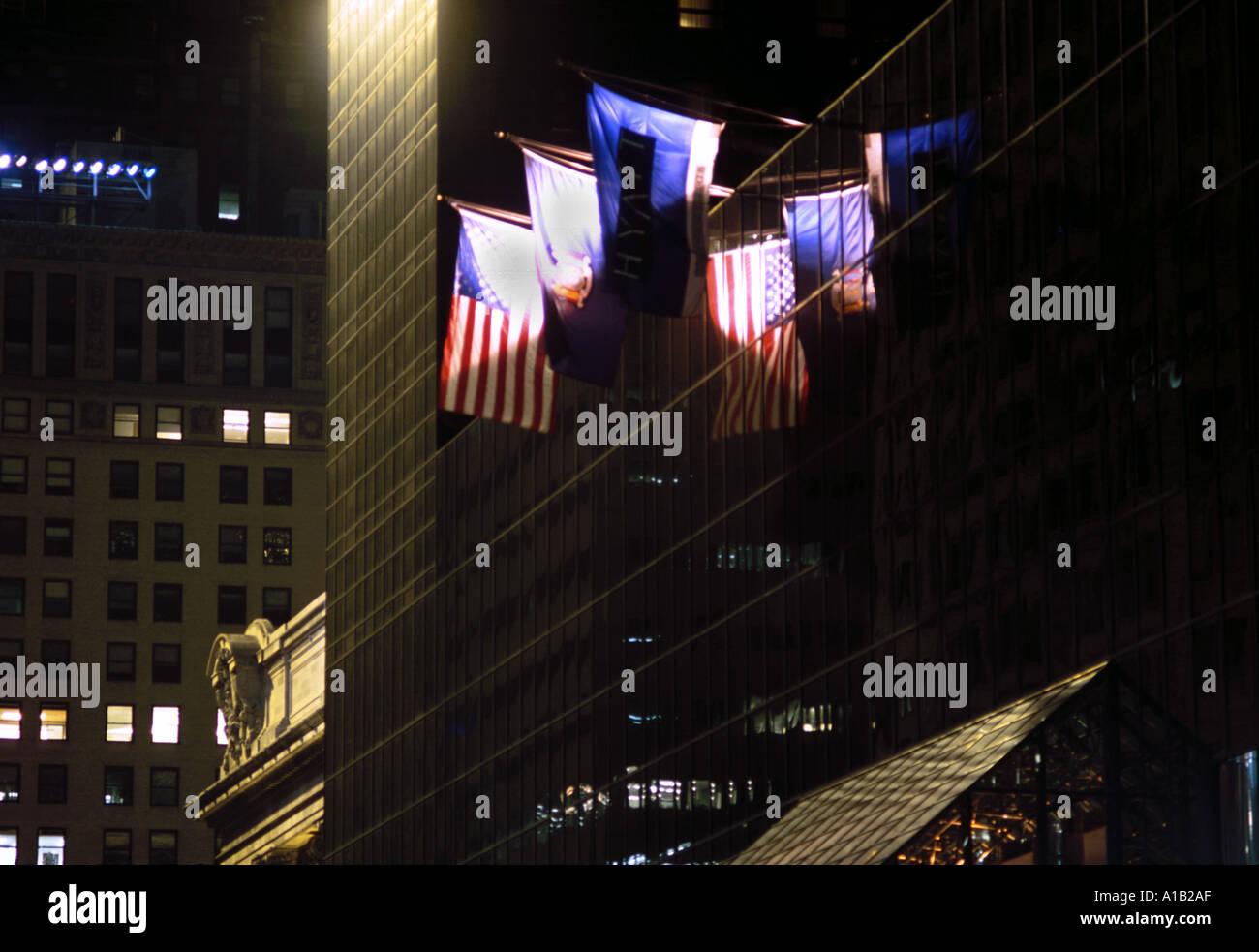 Flags flying at night outside New York City Grand Hyatt Hotel USA - Stock Image
