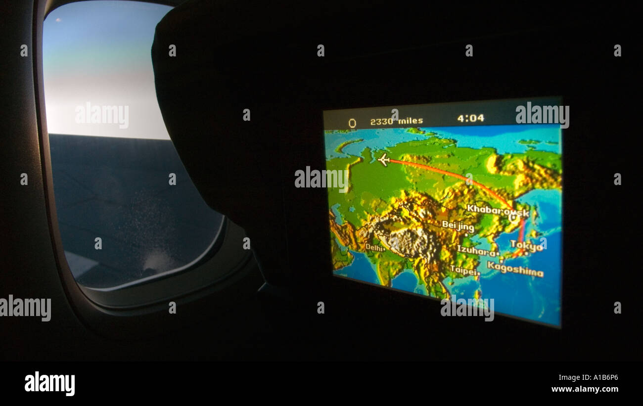 Seat monitor showing map of Eurasia and flight en route from Japan Darkened cabin with window and view of the Boeing 747 wing - Stock Image