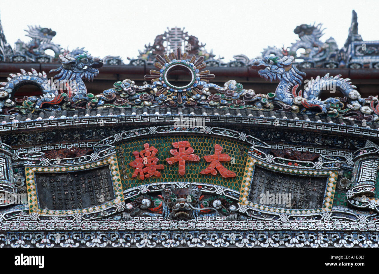 Detailo of a roof facade decorated with mosaic with dragons on top Imperial City Hue Vietnam - Stock Image
