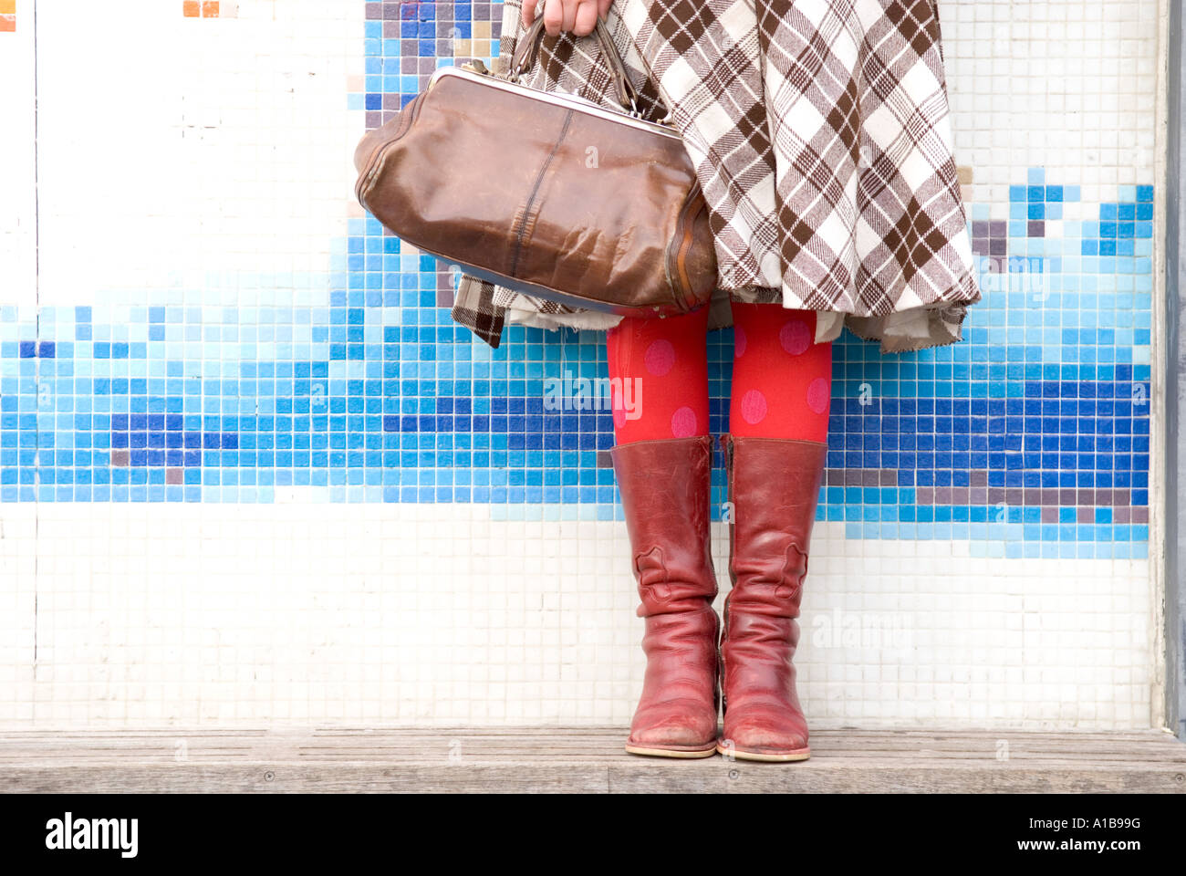 a cropped view of a female's legs standing against a modern wall covered with elegant brightly coloured mosaic - Stock Image