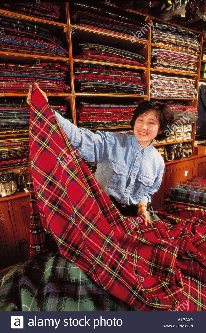 A JAPANESE CUSTOMER ENJOYS CHOSING A TYPE OF PLAID AT THE PIOB MHOR TARTAN SHOP AT BLAIRGOWRIE - Stock Image