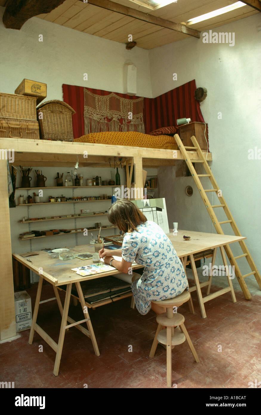 Artist working at trestle table below platform bed in ...