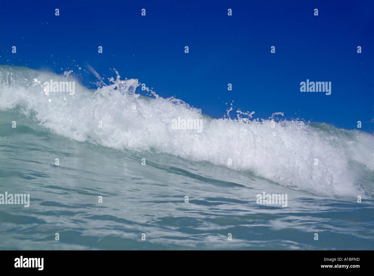 Crashing foamy waves in the blue ocean waters. - Stock Image