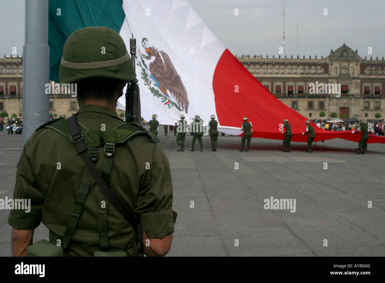 A soldier stands guard during the daily lowering of the flag in the Zocalo of Mexico City, Mexico. - Stock Image
