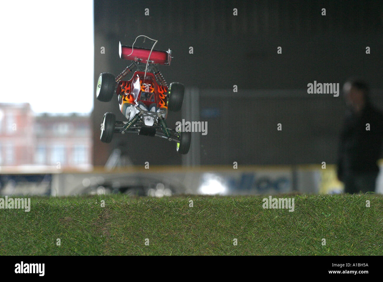 Off road buggy radio control car racing buggy in the air over a jump indoor grass track Belfast Northern Ireland - Stock Image