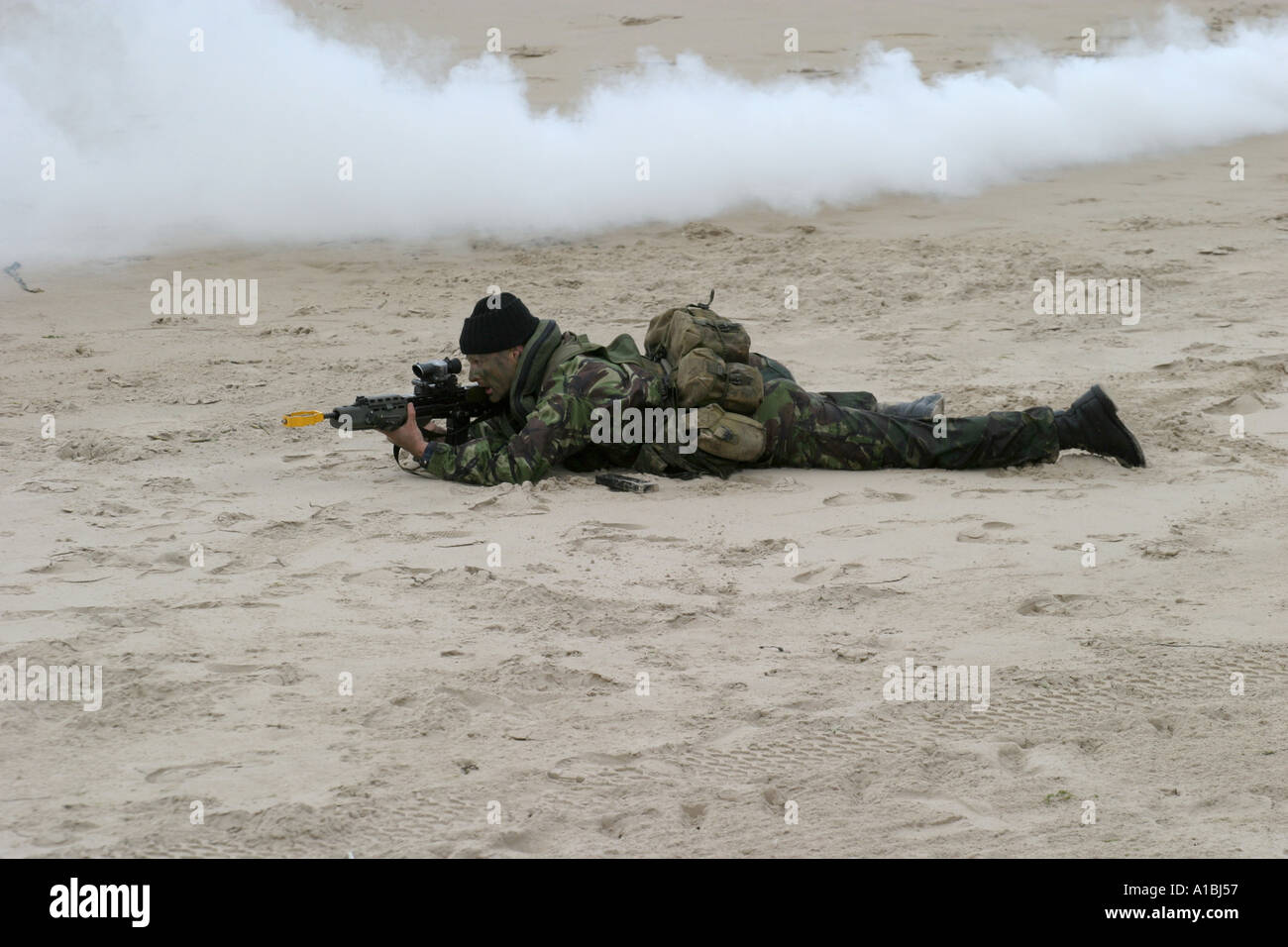 Royal Irish Regiment soldier takes up sniper position in smoke during mock beach assault exercise on Portrush beach West Strand - Stock Image