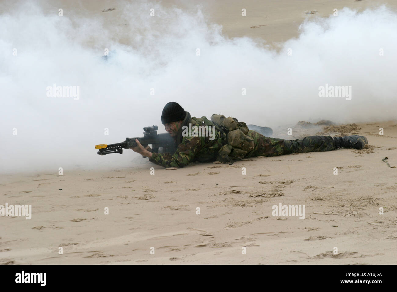 Royal Irish Regiment soldier takes up sniper position in smoke during mock beach assault exercise on Portrush beach - Stock Image