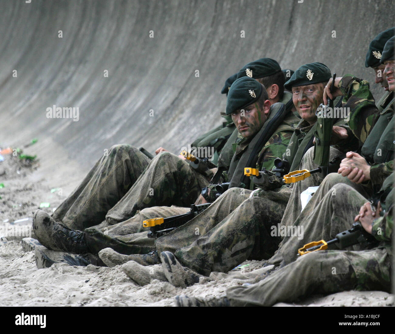 Royal Irish Regiment RIR soldiers relax under the sea defences at Portrush West Strand after their mock beach assault during military exercise - Stock Image
