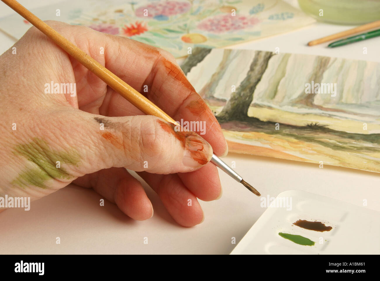 An artists hand with paintings and a paint tin - Stock Image