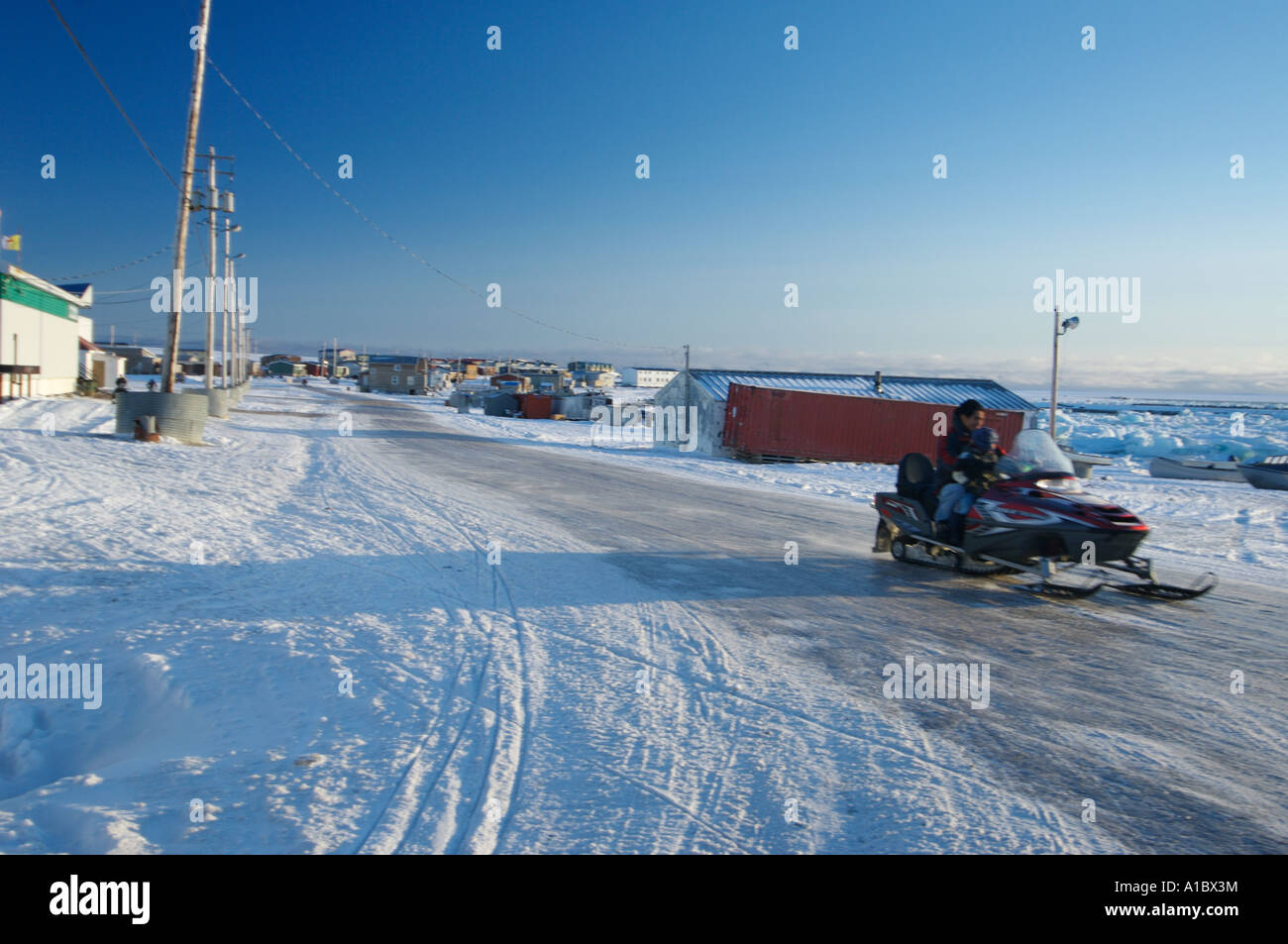 Snowmobile or skidoo Inuit and child on the main road in Igloolik or Iglulik village, Nunavut northern Canada October - Stock Image