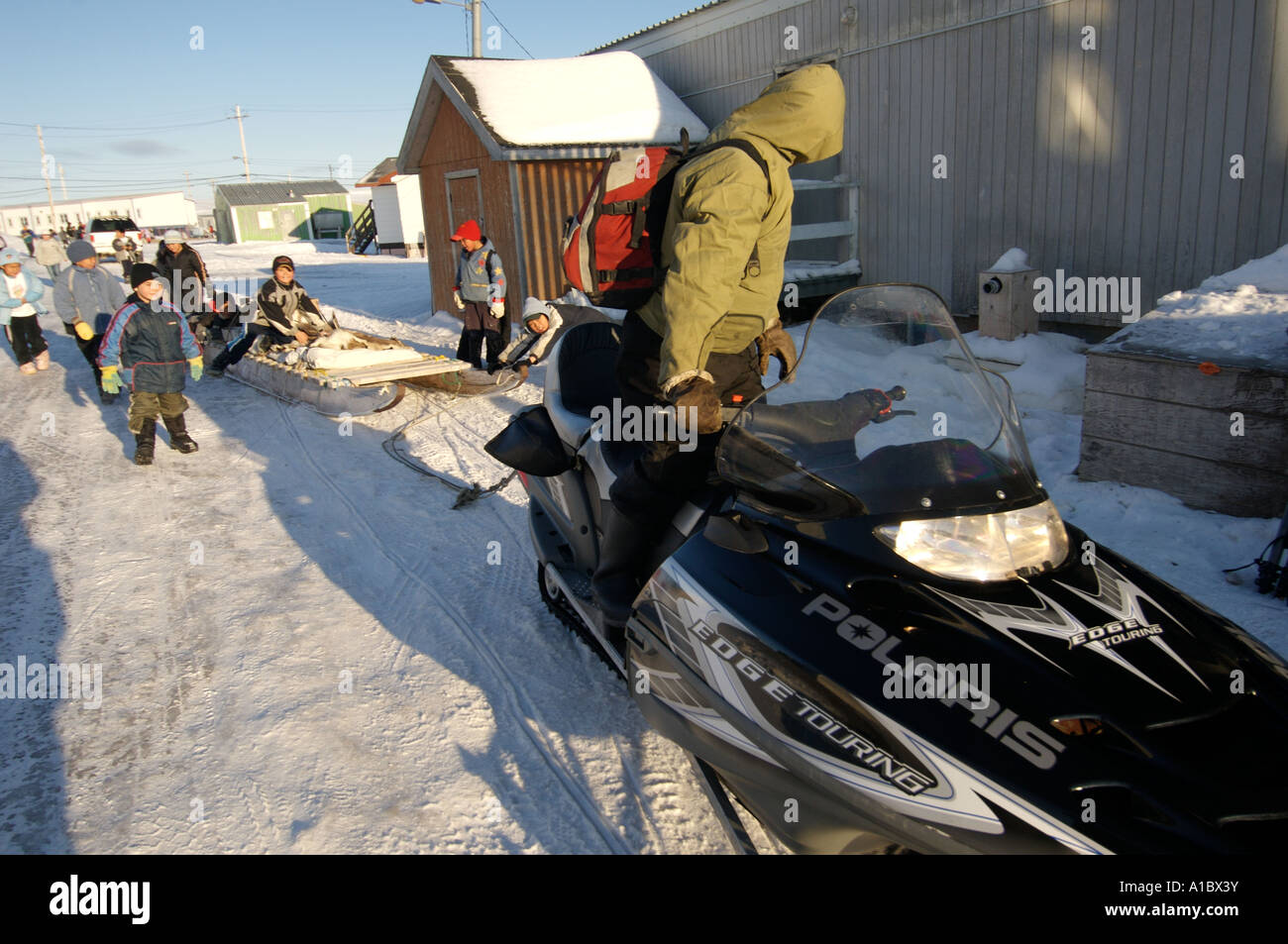 Snowmobile pulling traditional komatiq or komatek Children playing on the way home from school at lunchtime in Igloolik - Stock Image