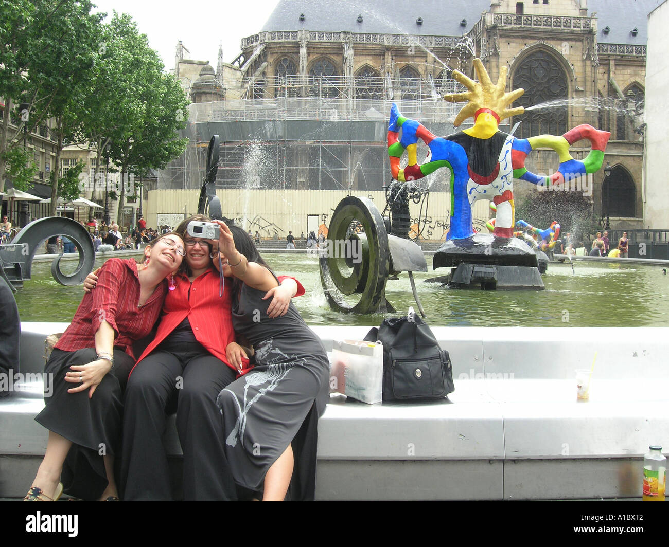image no 1 of three female students taking digital picture in front of Tinguely fountain at Place Igor Stravinsky Stock Photo
