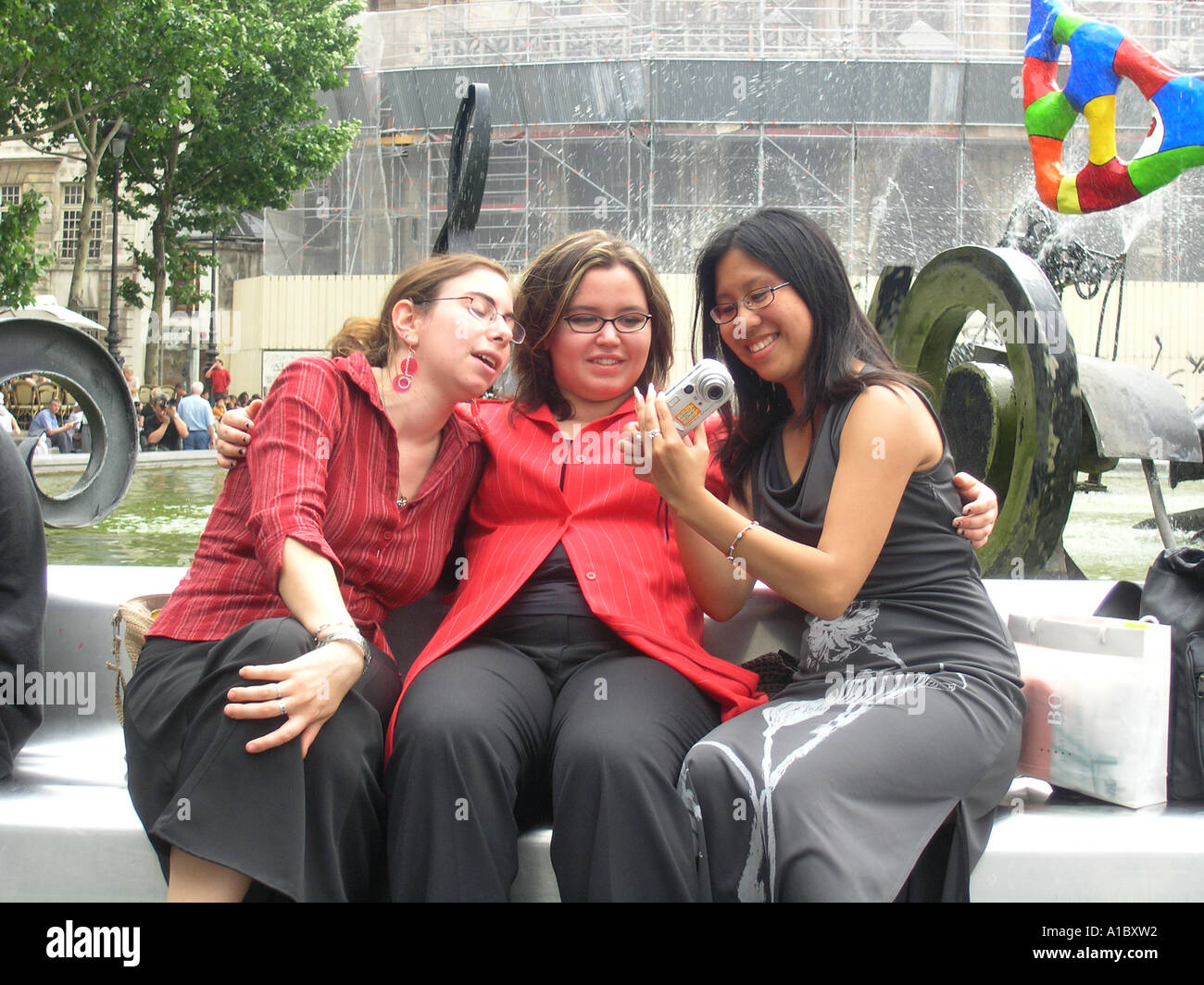 image no 2 of three female students taking digital picture in front of Tinguely fountain at Place Igor Stravinsky Stock Photo