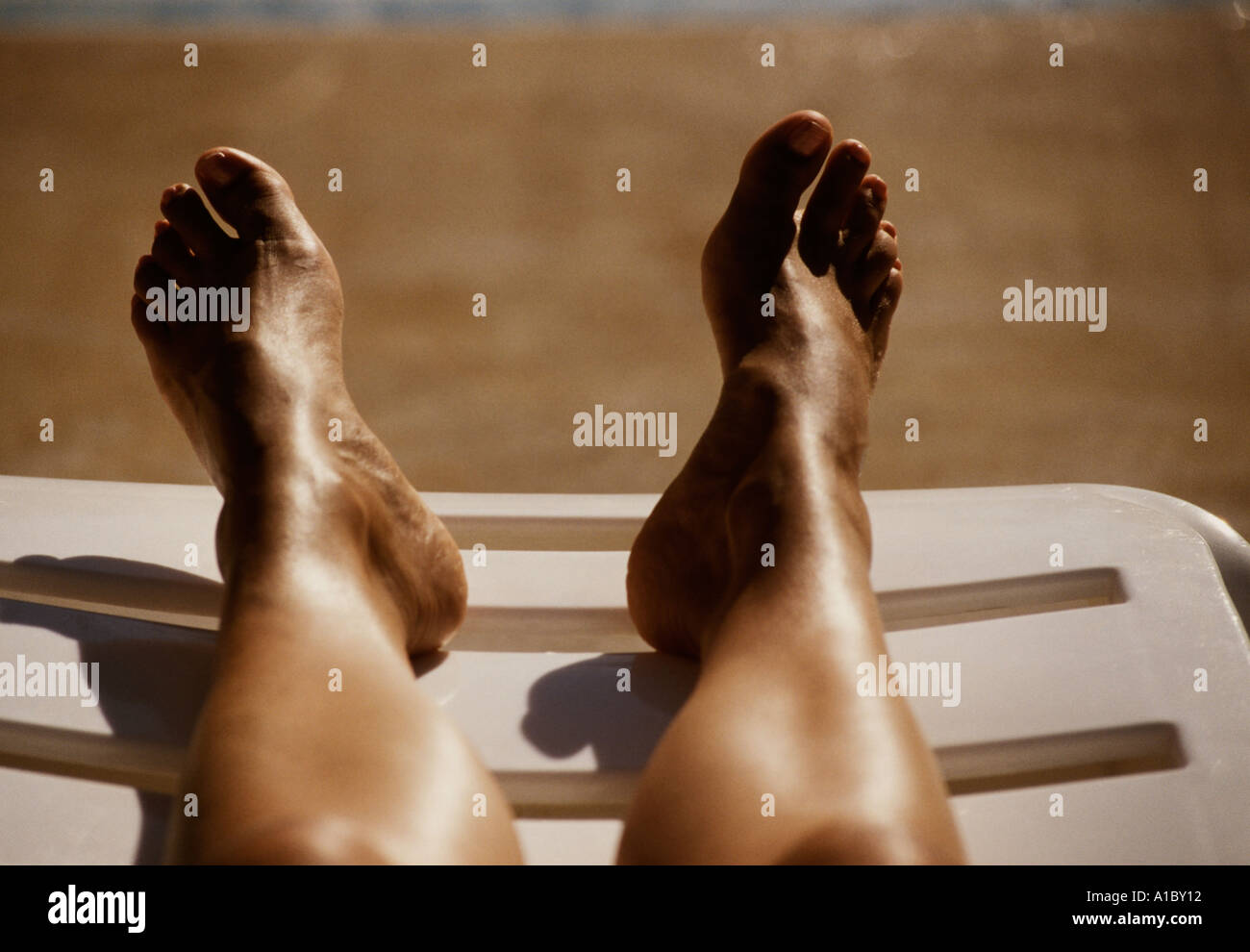 a pair of legs and feet on a sunlounger - Stock Image