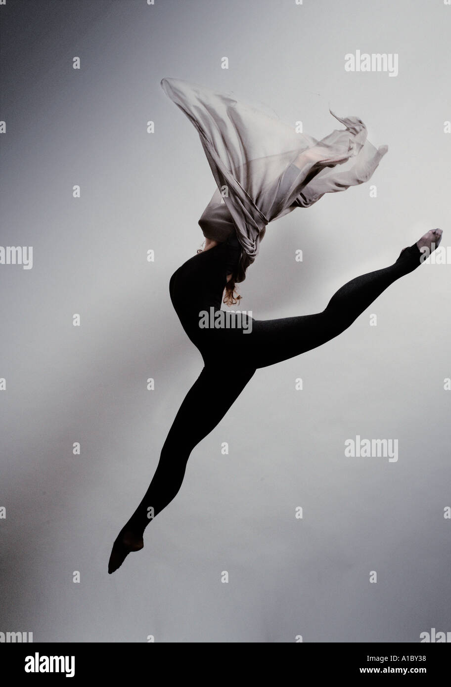 female ballet dancer leaping with a silk scarf - Stock Image