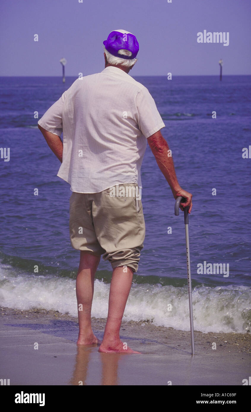 Elderly man alone Hand on a walking cane with rounded shoulders Standing at water edge gazing towards the horizon - Stock Image