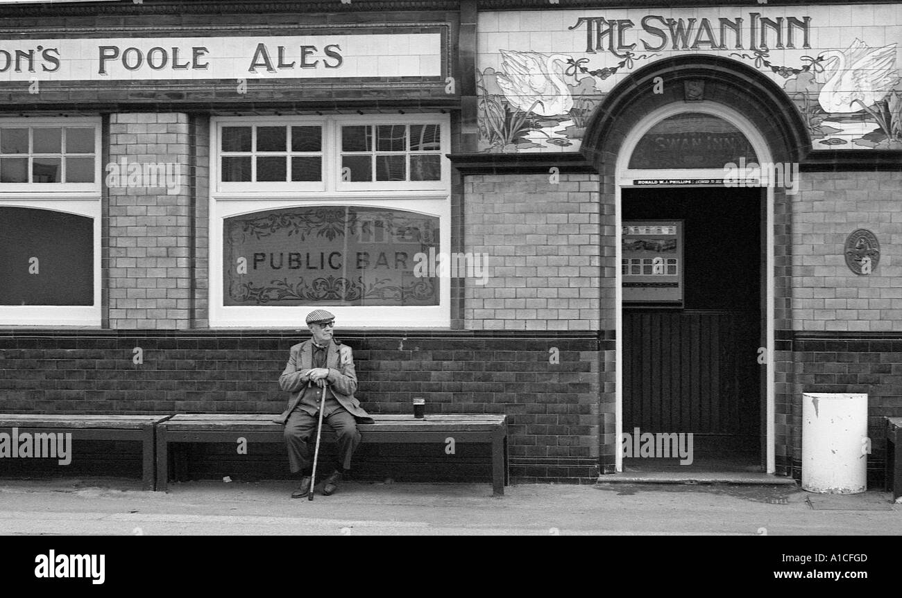 Old man with pint of beer sitting on bench outside the Swan pub. - Stock Image