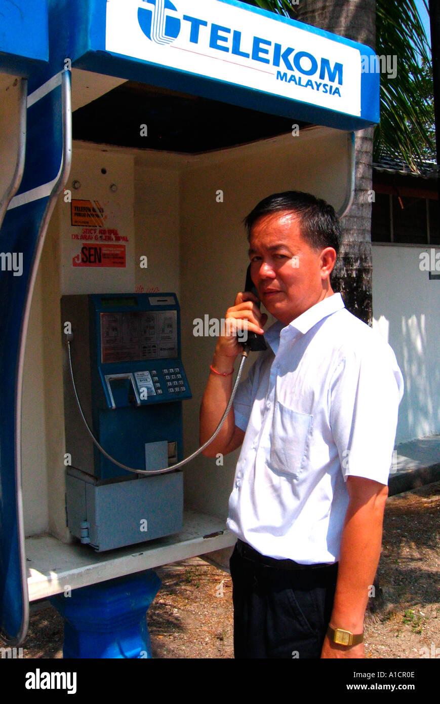 Man uses public Telekom Malaysia telephone Batu Ferringhi beach Penang - Stock Image