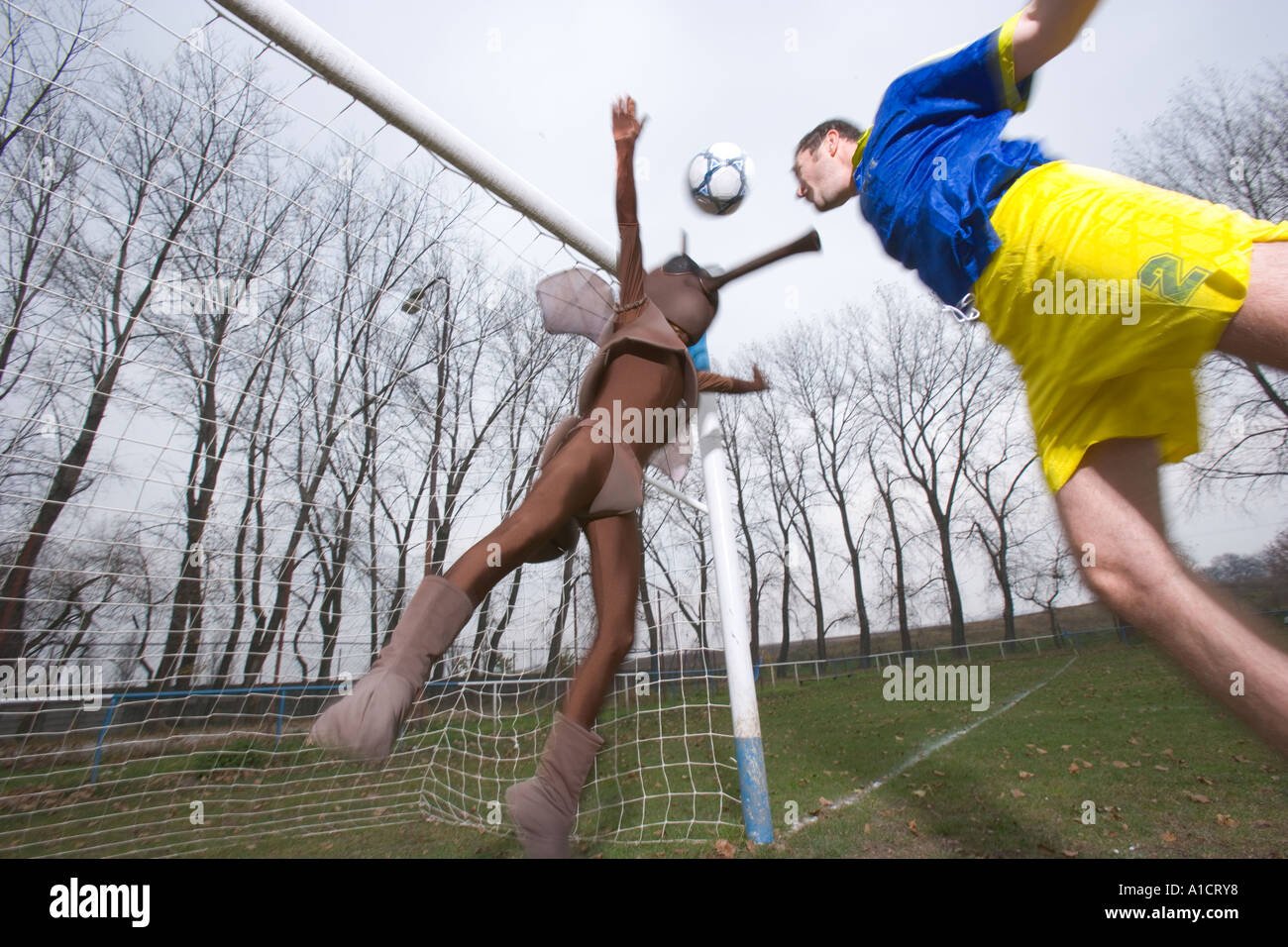 Football player in the air heading the ball to the goal post defended by a goal keeper in mosquito costume - Stock Image