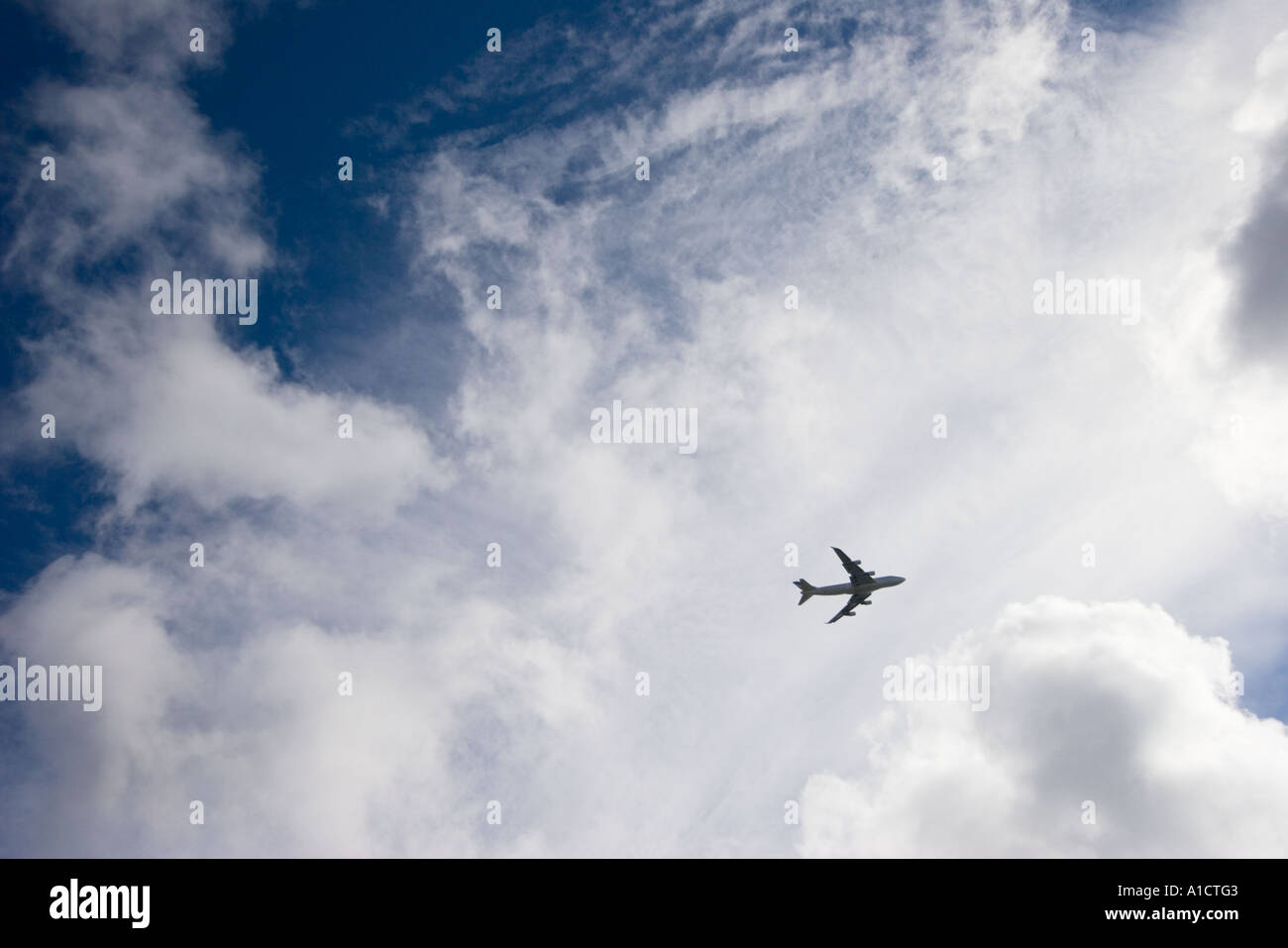 A silhouette of a flying jumbo jet against a partly cloudy sky Stock Photo