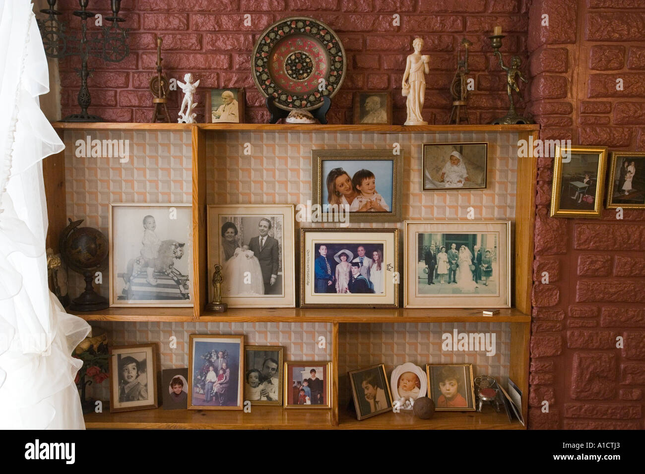 Still Life Of Framed Photographs And Statuettes In A Shelf Placed