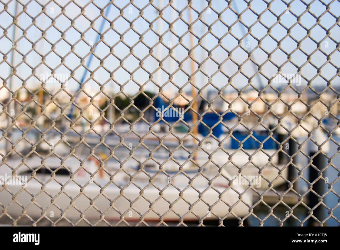 Yacht harbor behind chain link fence San Francisco California United States of America - Stock Image