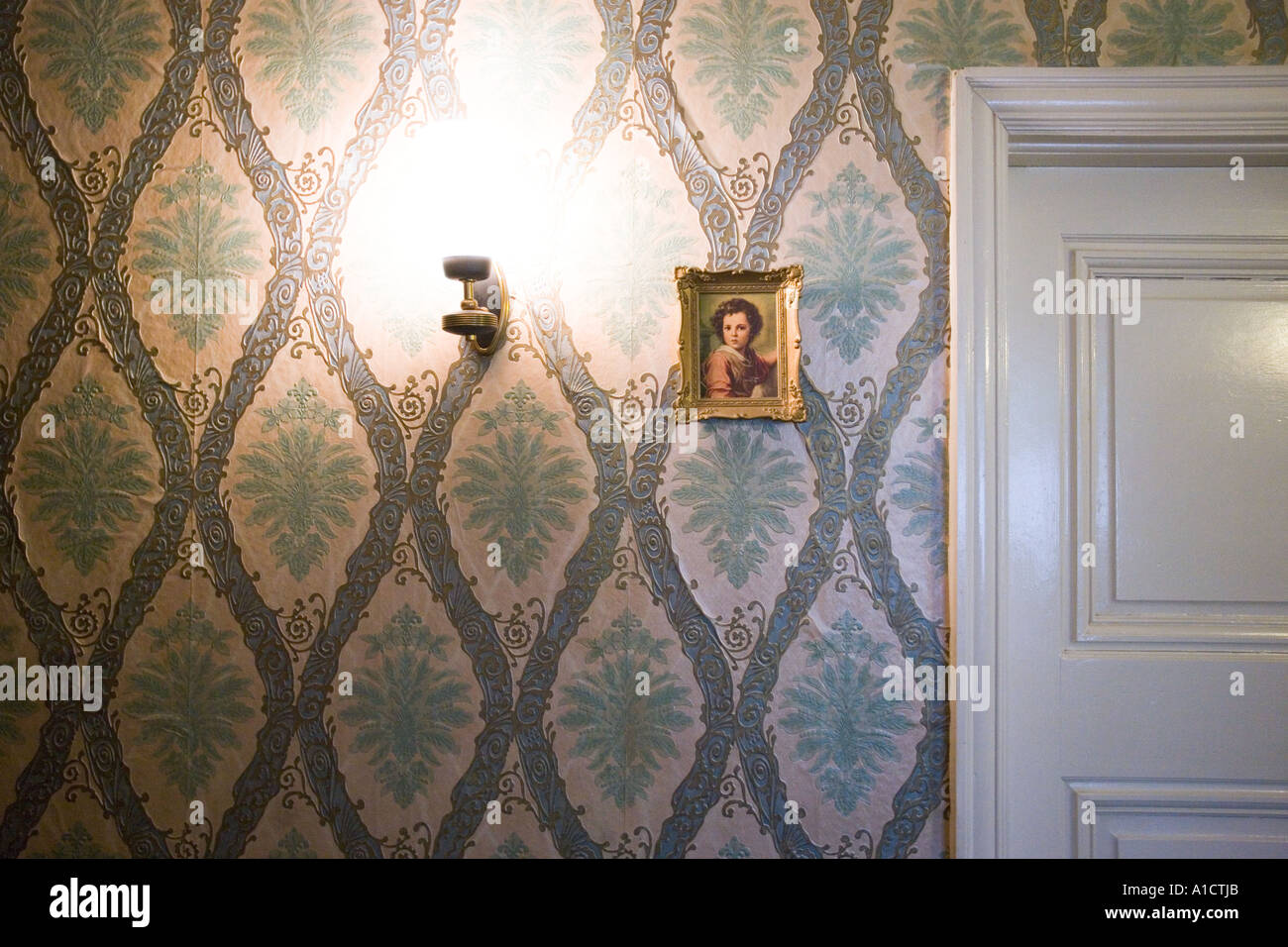 Bright lamp glowing next to a small framed baroque painting hung on a wall with floral pattern near the door - Stock Image