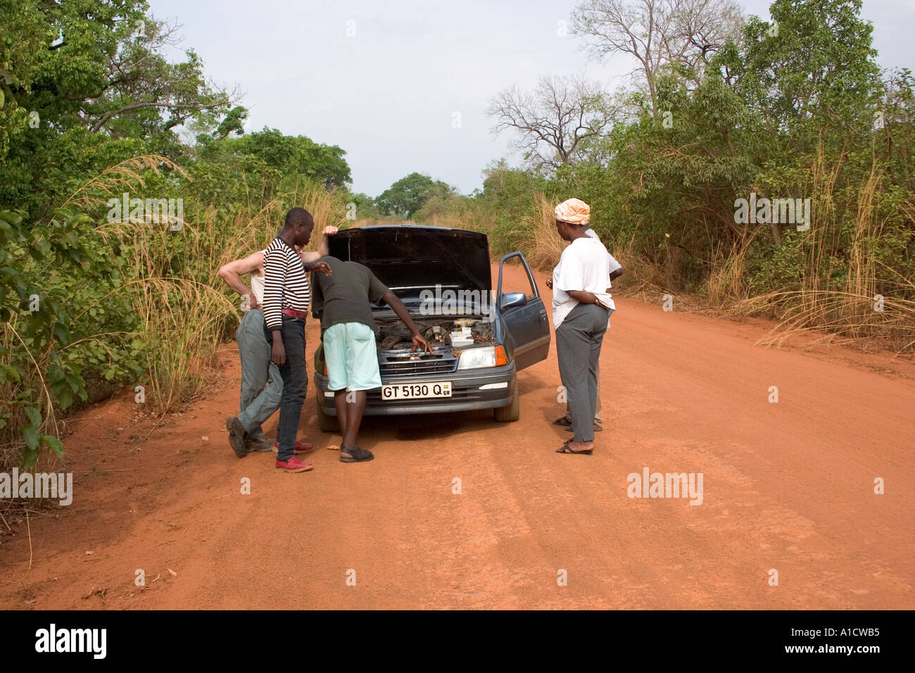 Passersby assisting driver of a brokendown car on a laterite road in Northern Ghana - Stock Image