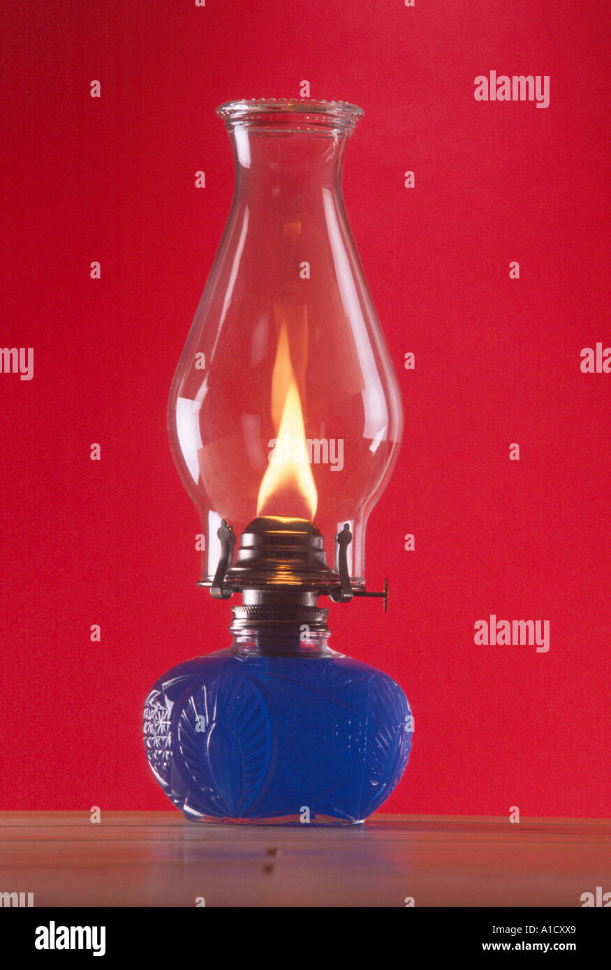still life glass oil lamp with flame and blue oil in cut glass base red background PR CL - Stock Image